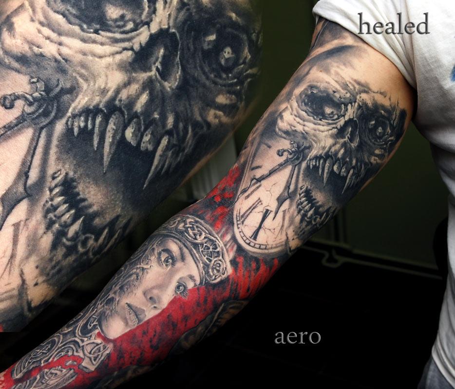 Tattoo von Totenkopf mit langen Zähnen, einer Uhr und einem Gesicht über den ganzen Arm