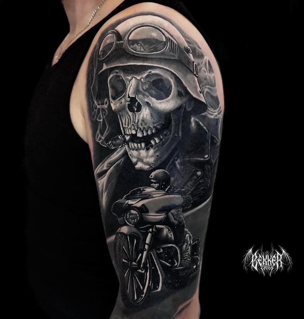 Oberarm Tattoo mit einem Totenkopf der Raucht und ein Helm auf hat und der gerade am Motorrad fahren ist