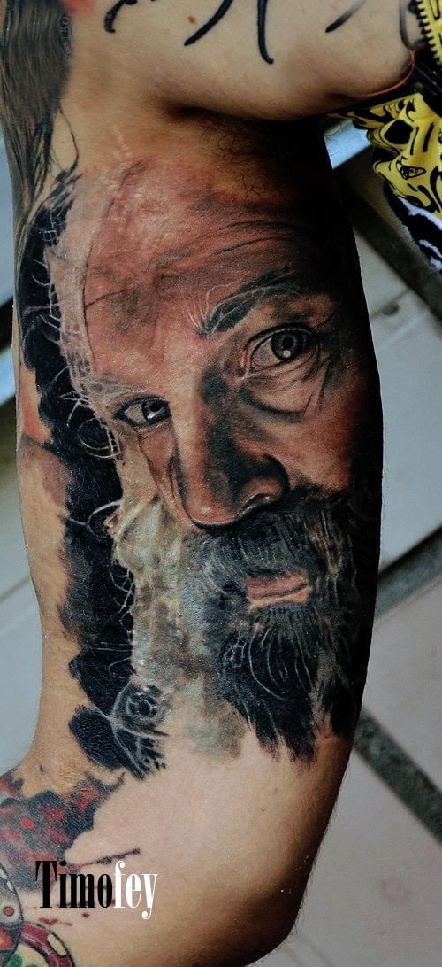Mann mit Bart Oberarm Tattoo