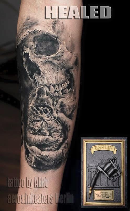 Tattoo von einem Totenkopf und einer Babykatze, welche in Händen gehalten wird.