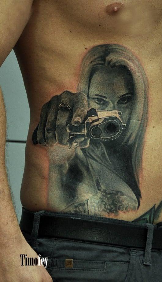 Bauch Tattoo von einer Frau die eine Waffe vor ihrem Gesicht hält