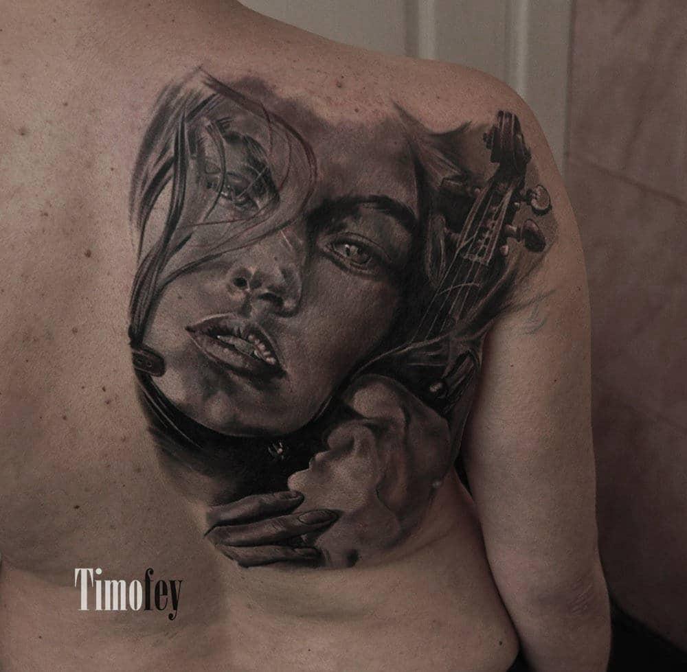 Gesicht einer Frau mit einer Geige die festgehalten wird von Ihr Tattoo
