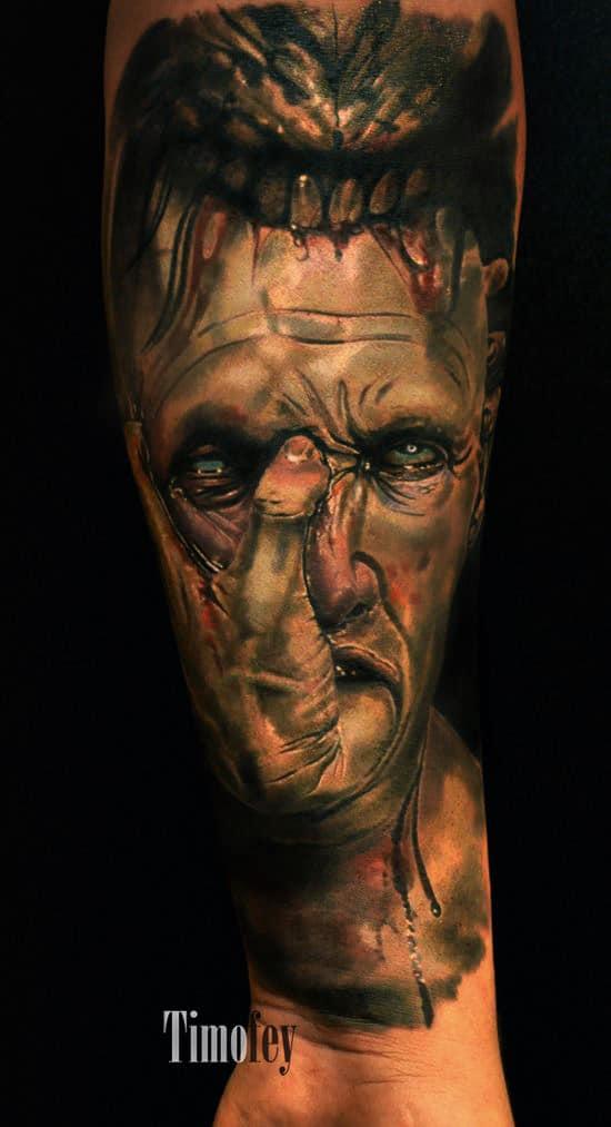 Schlange die ein Kopf eines Menschen im Maul hat, Aus dem Mund des Menschen sticht ein Finger auf die Stirn des Mannes Tattoo