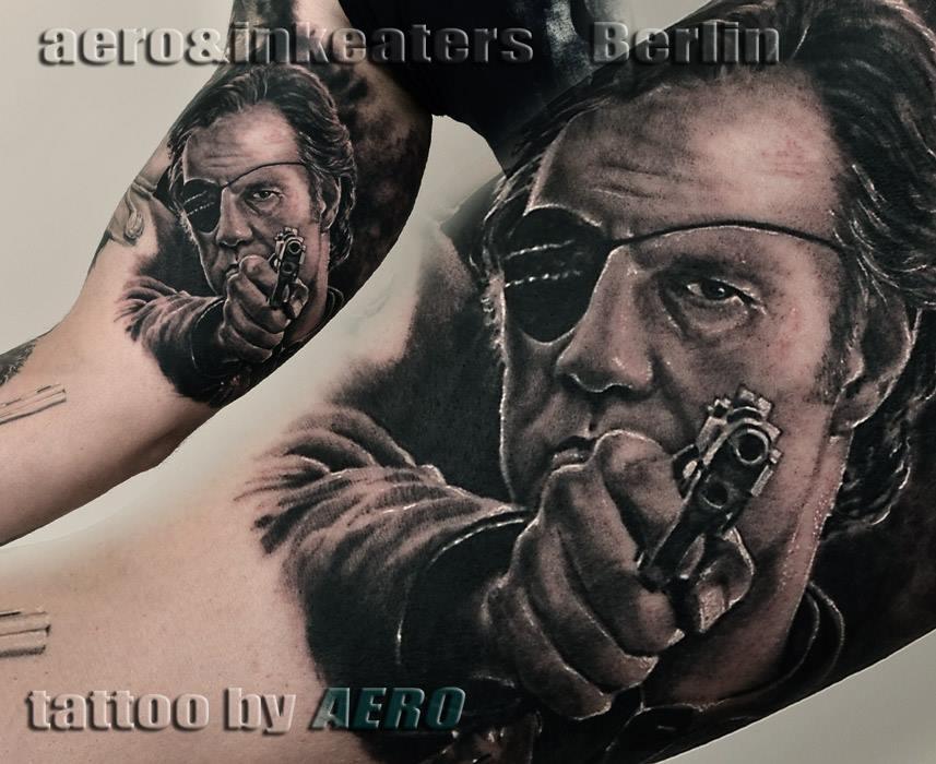 Tattoo von Person mit Augenklappe und nach oben gerichteter Pistole