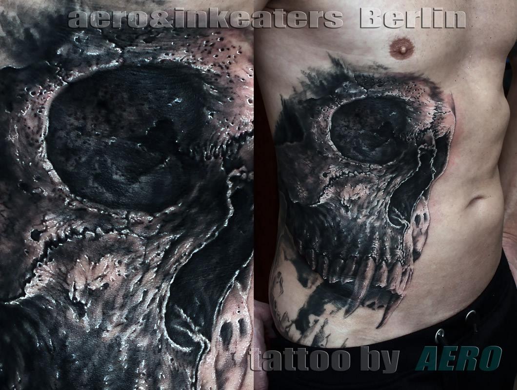 Tattoo von Totenkopf mit spitzen Zähne auf der rechten Bauchseite