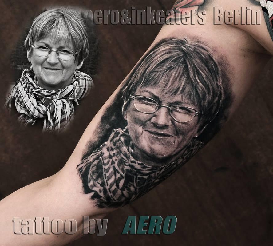 Tattoo von einer älteren Frau, die eine Brille trägt, auf dem Oberarm