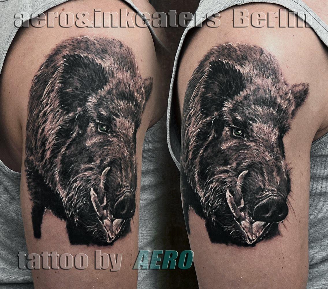 Tattoo von einem Wildschweinkopf auf dem Oberarm
