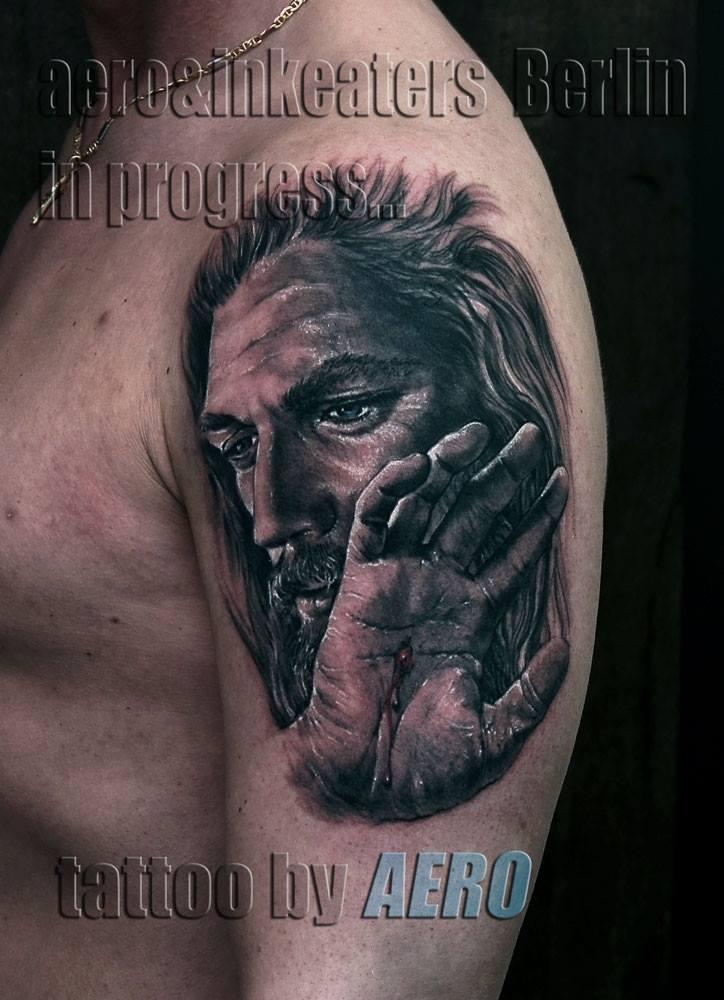 Tattoo von männlichen Gesicht mit langen Haaren und Bart und einer Wunde an der Hand