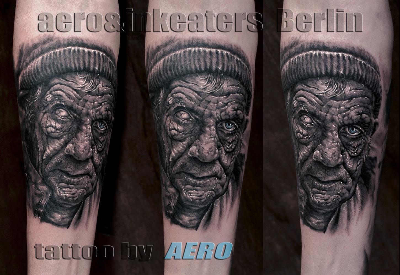 Tattoo von einem faltigen älteren Gesicht, mit einer Kopfbedeckung, auf dem Unterarm
