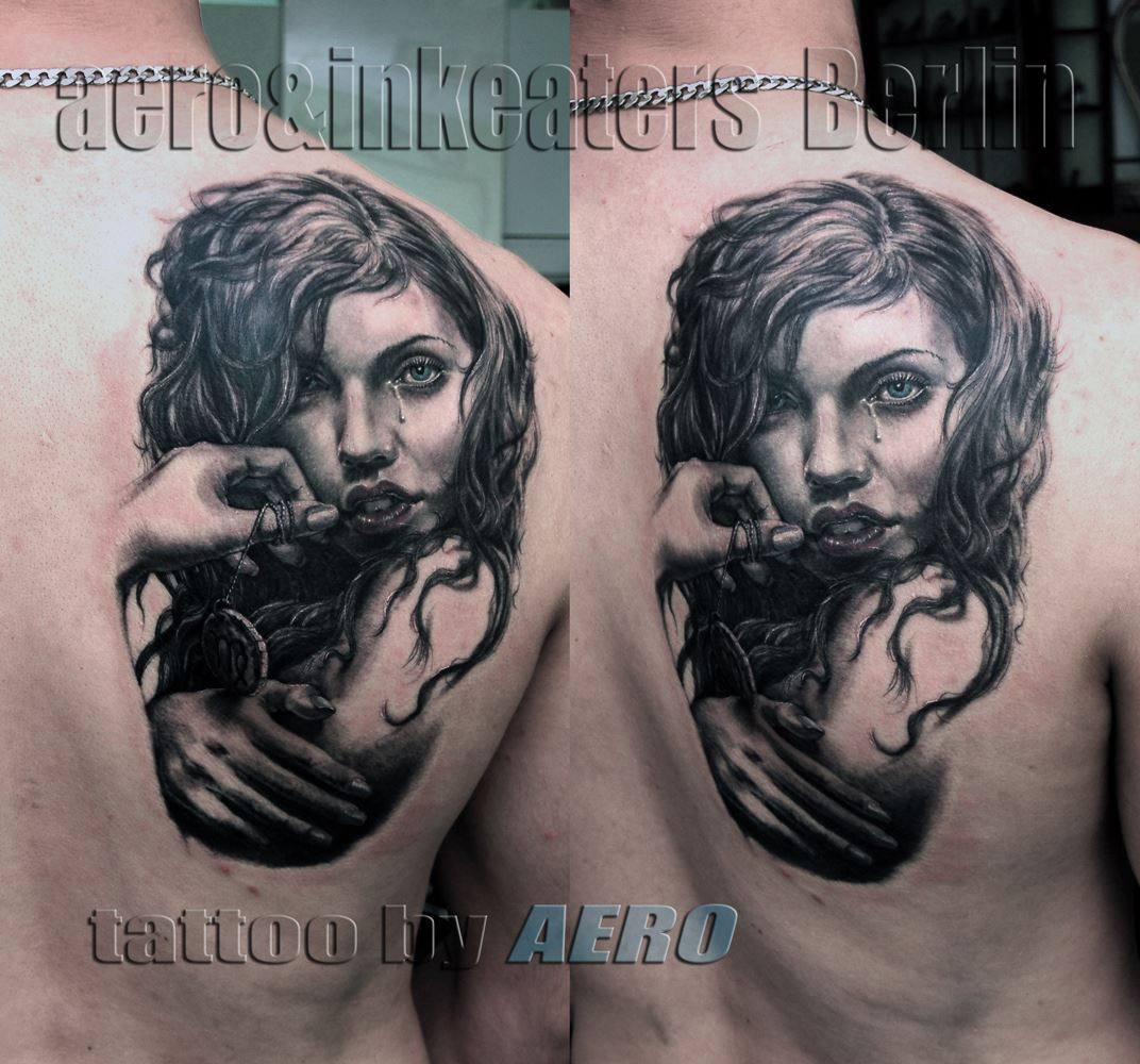 Tattoo von einer Frau, mit Tränen unter dem Auge, auf dem rechten Rücken.
