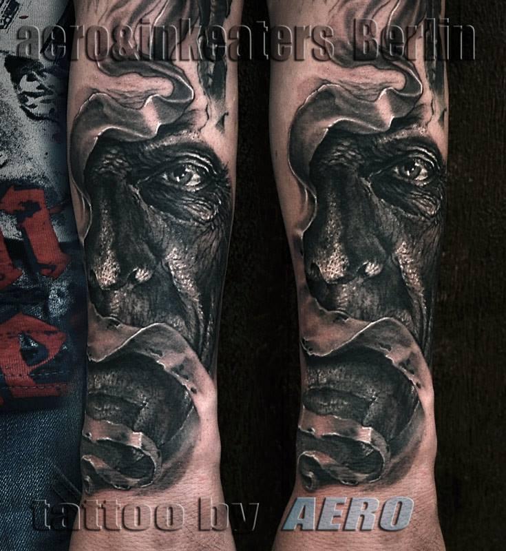 Tattoo von einem dunklen, leicht verschleierten, Gesicht.