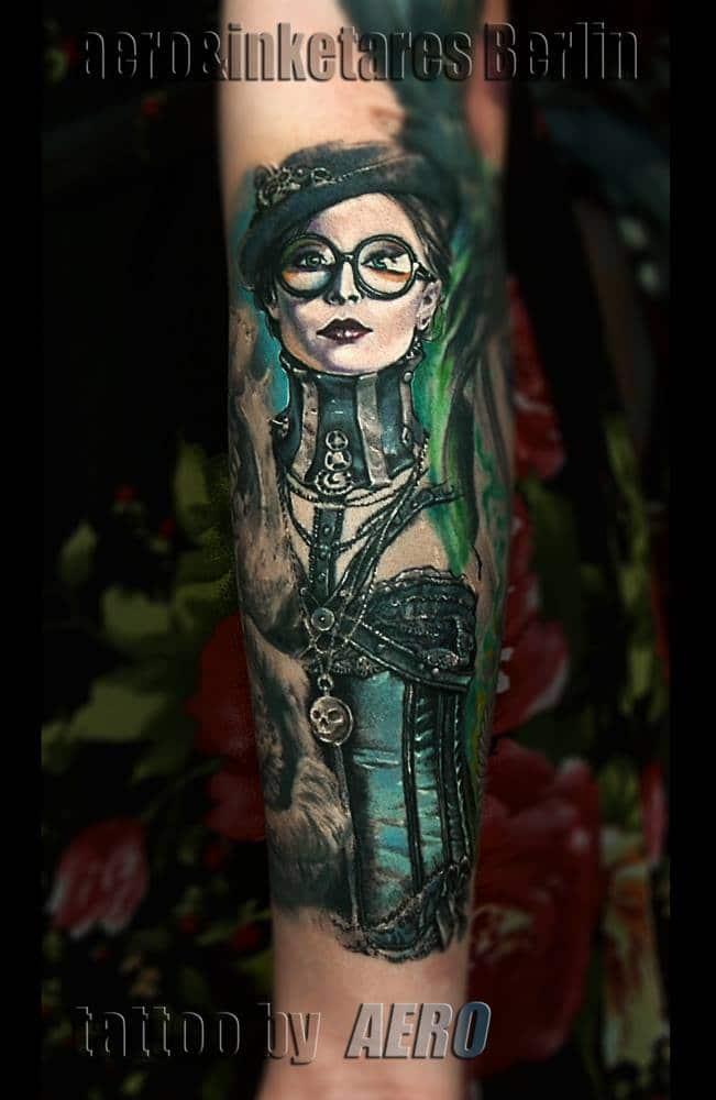 Tattoo von einer Frau, mit einer runden Brille und einer Kopfbedeckung.