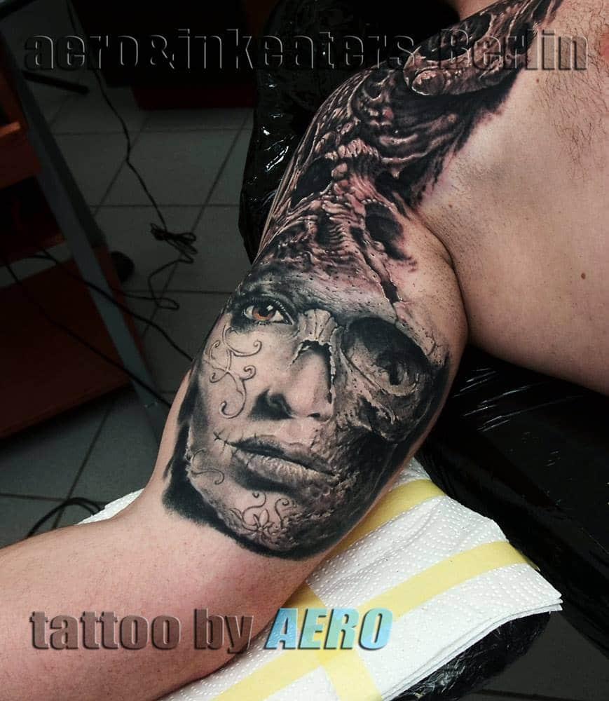 Tattoo von einem weiblichen Gesicht, welches halb aufgerissen ist auf dem Oberarm.