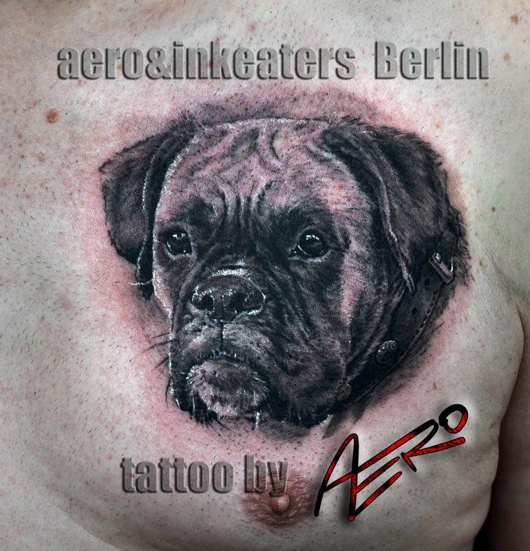 Tattoo von einem Hundekopf auf der linken Brust.