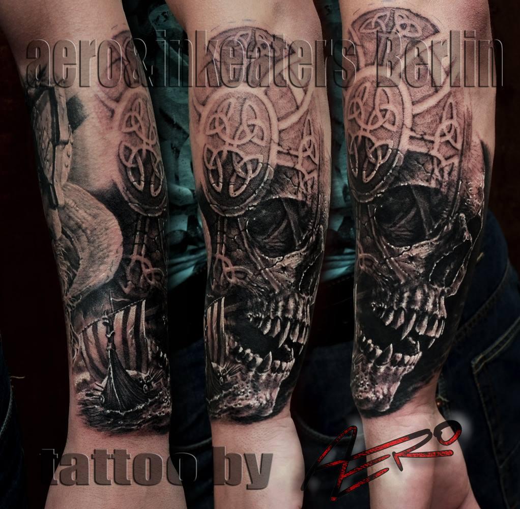 Tattoo von einem Totenkopf und einem Symbol auf dem Unterarm.