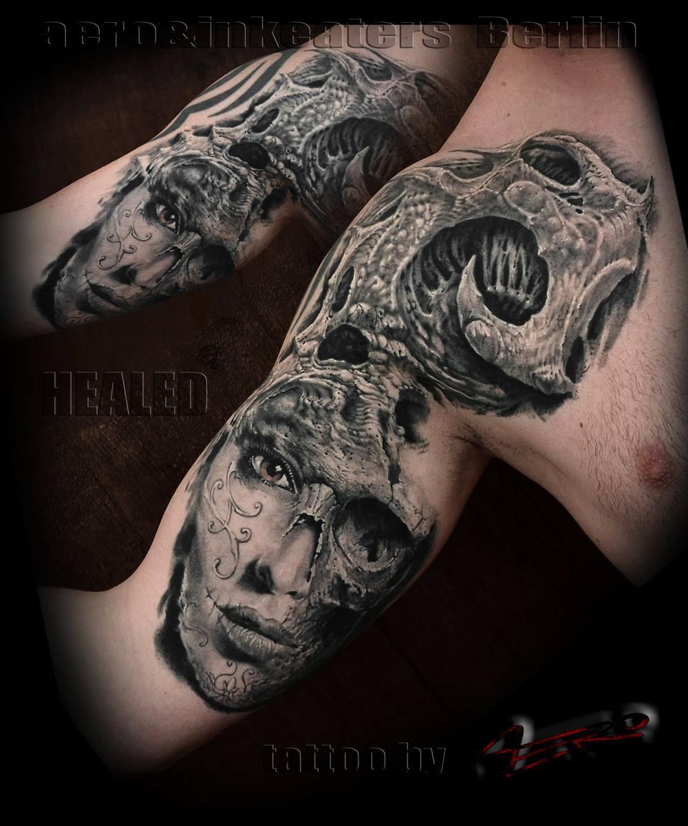 Tattoo von einem weiblichen Gesicht, welches halb aufgerissen ist, auf dem Oberarm.