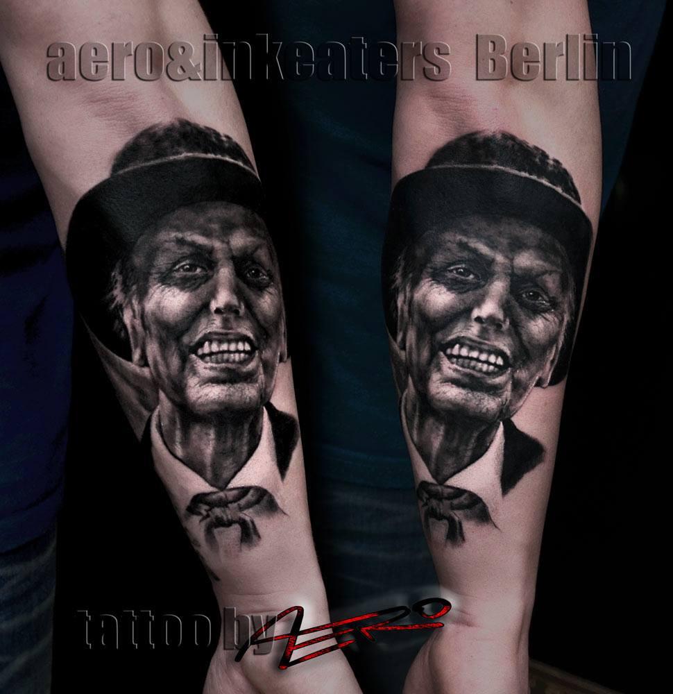 Tattoo von einer Person, mit geöffneten Mund und einem Hut, auf dem Unterarm.