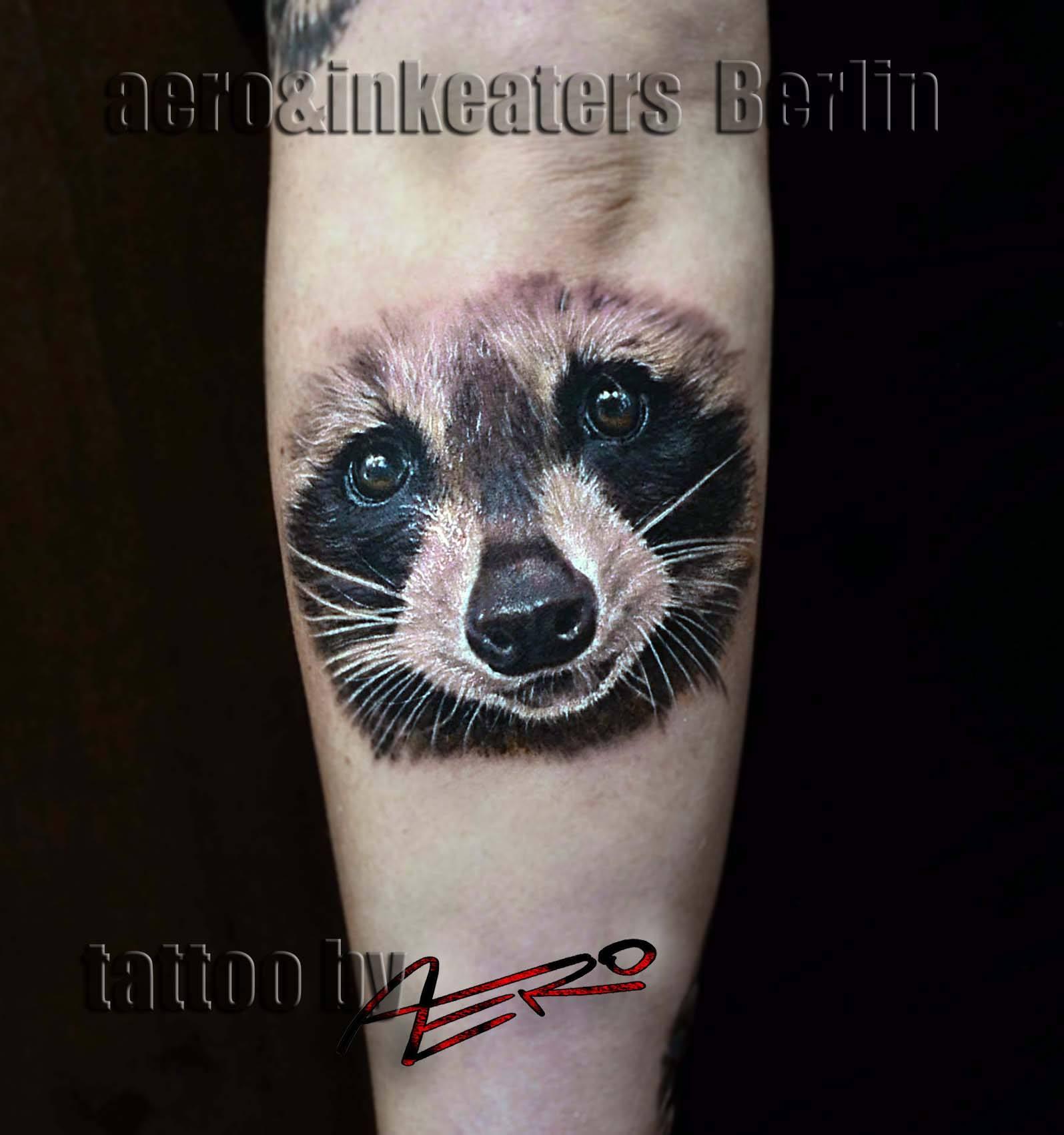 Tattoo von einem Waschbär Kopf auf dem Unterarm.