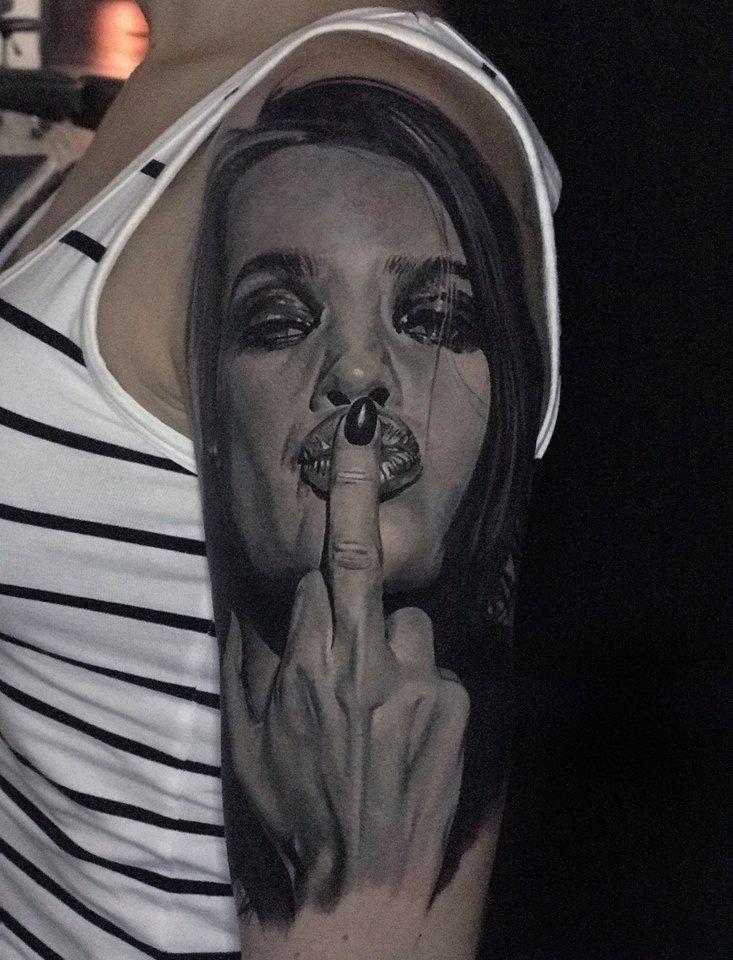 Frau die ihren Mittelfinger küsst Tattoo