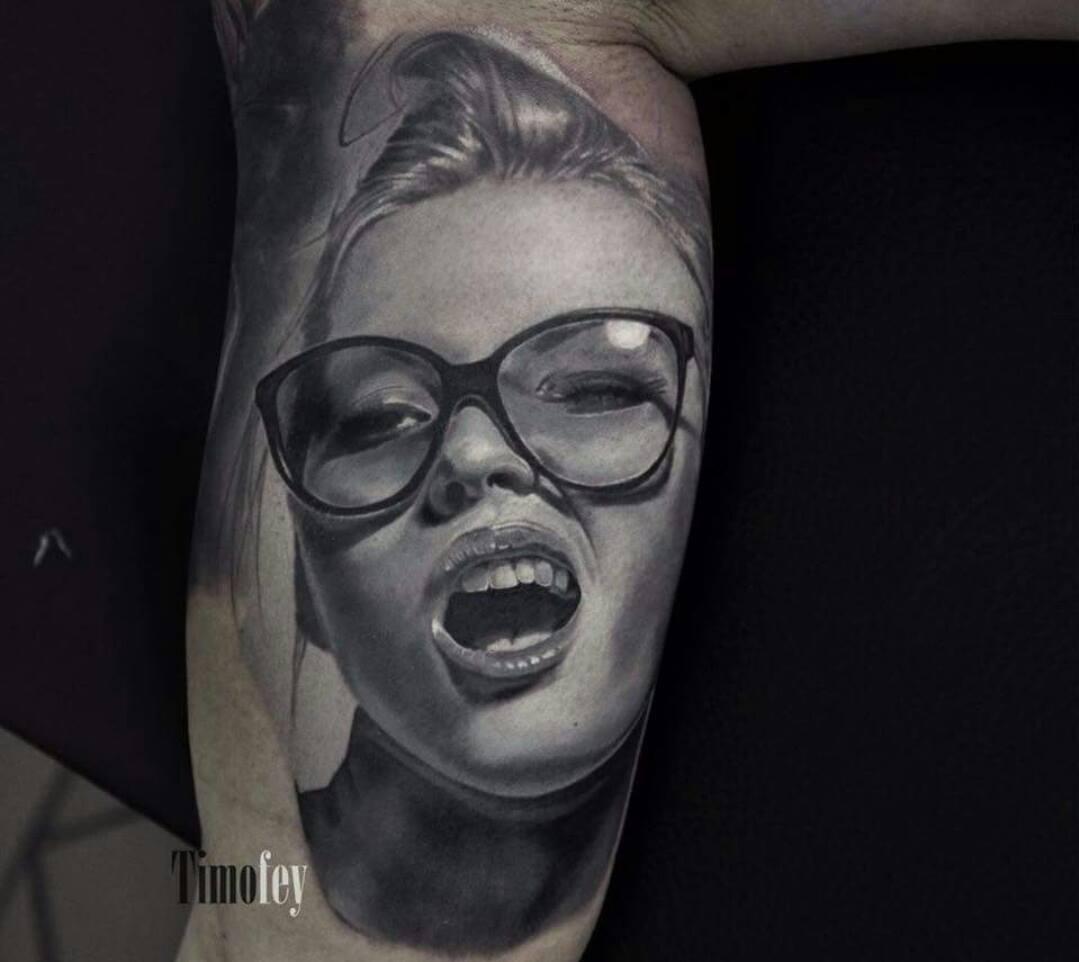 Frau mit Brille und offenen Mund Tattoo
