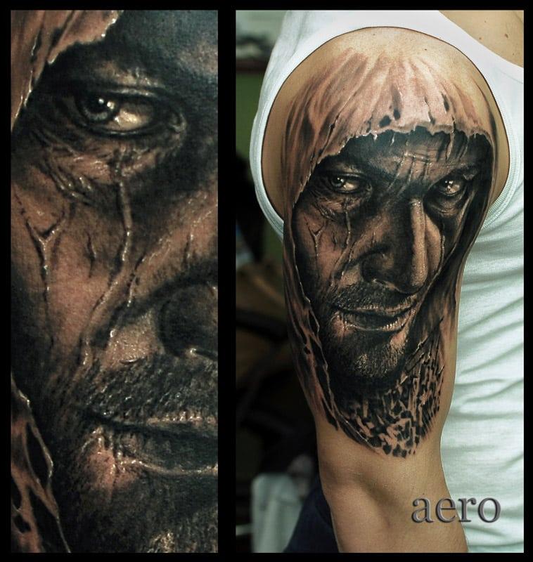 Dunkles Tattoo von männlichen Gesicht auf dem Oberarm