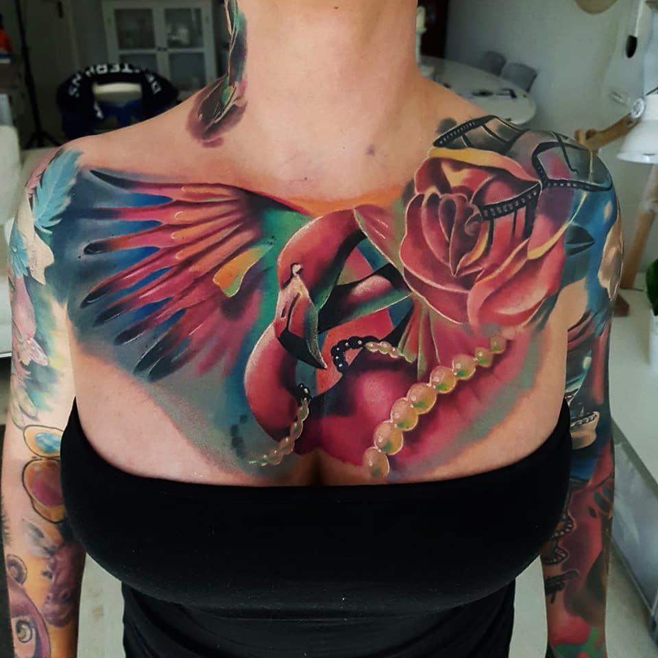Brust Tattoo mit einem Vogel und Schmuck