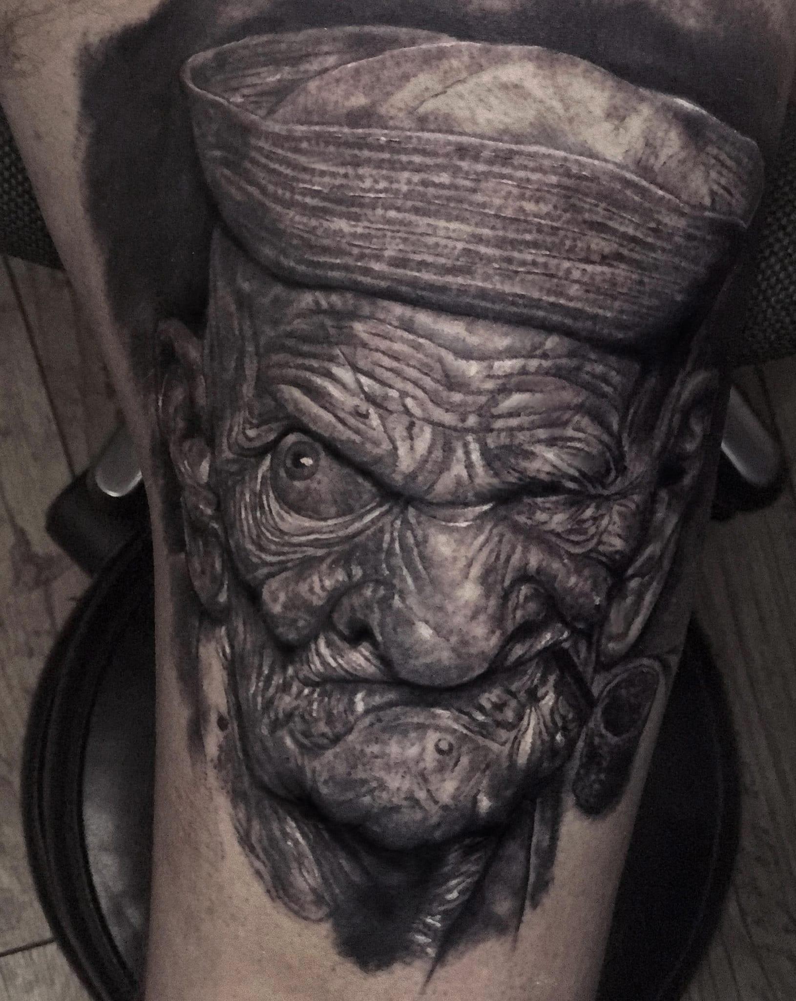 Tattoo von einem altem Mann der eine Pfeife raucht