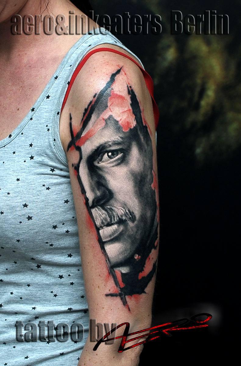 Tattoo von einem ausgeschnittenen männlichen Kopf auf dem Oberarm