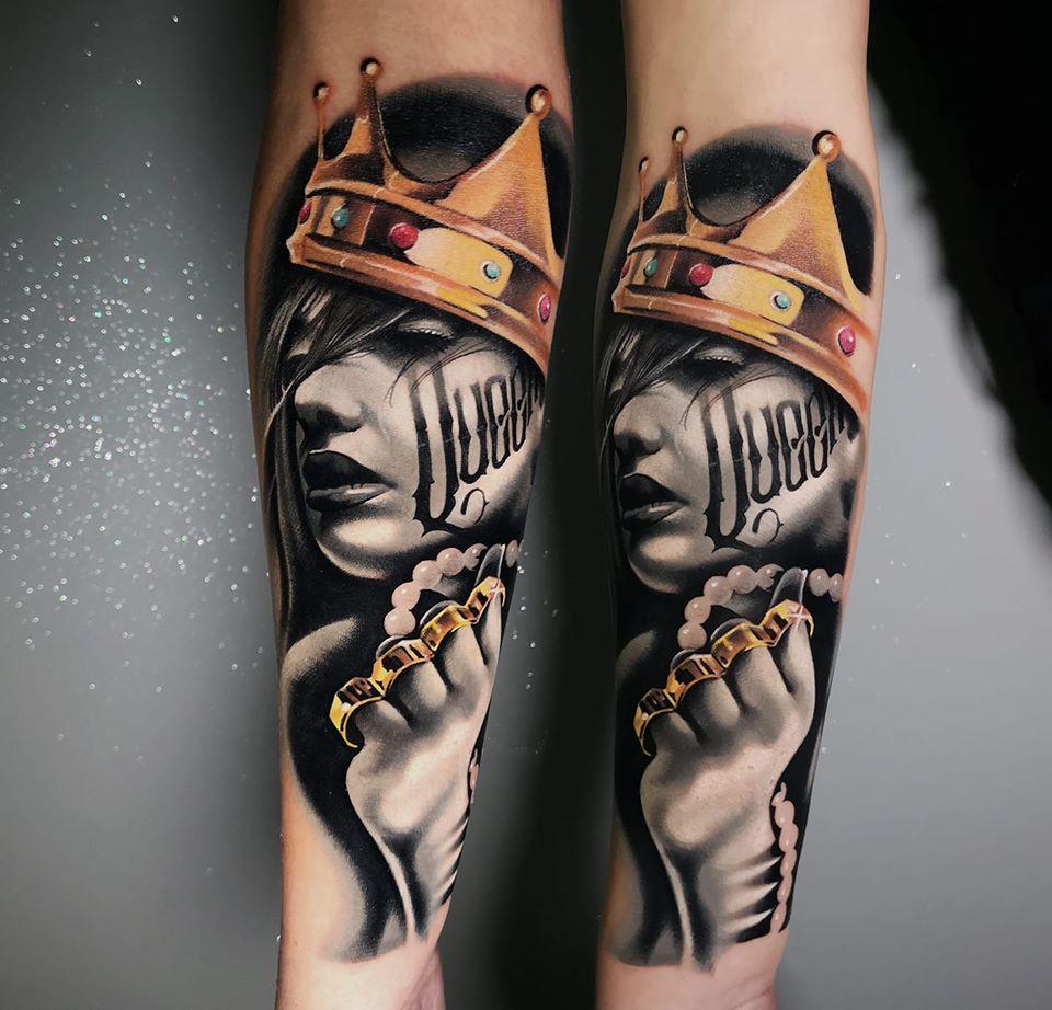 Frau mir einer Krone und im Gesicht eine Queen Aufschrift und Ringen Tattoo