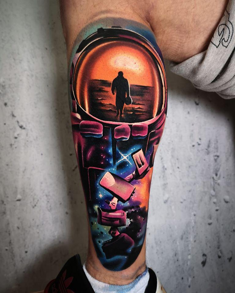 Tattoo an der Wade mit einer Person die Richtung Wasser läuft und da drunter Weltraum Details