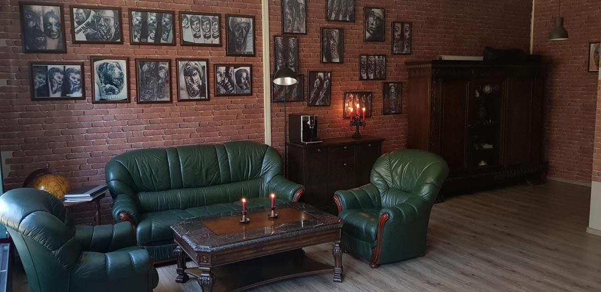 Wartezimmer mit dunkel grüner Leder Couch und einem Holztisch